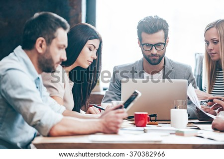 Double-checking all the documents. Group of four young people reading and looking through charts while sitting at the table in office - stock photo