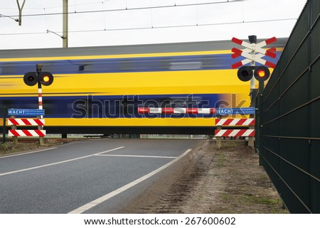 double deck passenger train at railroad crossing in the netherlands - stock photo