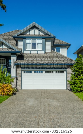 Double doors garage with nicely paved driveway. North America. Vertical. - stock photo