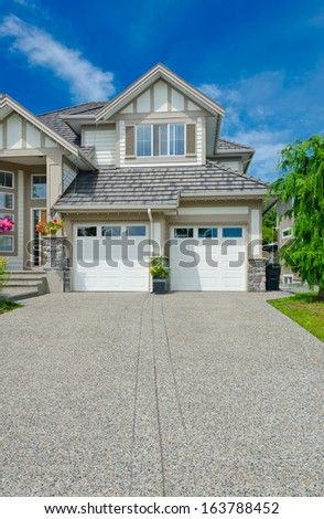 Double doors garage with wide and long driveway  in the suburbs of Vancouver, Canada. - stock photo