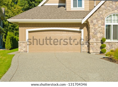 Double doors garage with wide and long driveway. North America. - stock photo