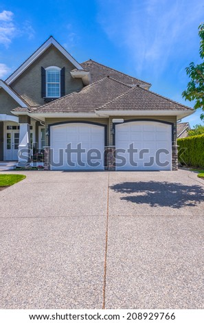 Double doors garage with wide long driveway. Vertical.