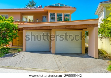 Double doors garage with wide, long nicely paved driveway. North America. - stock photo