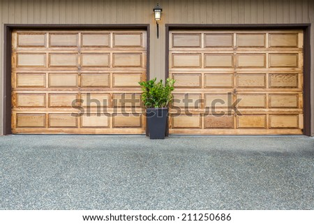 Double doors wooden garage with wide long driveway. - stock photo