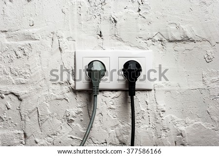 Double electrical socket with plugged cables on brick wall