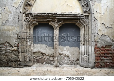 Double entrance of an old church is built in, the plaster ha fallen down, stones are visible.