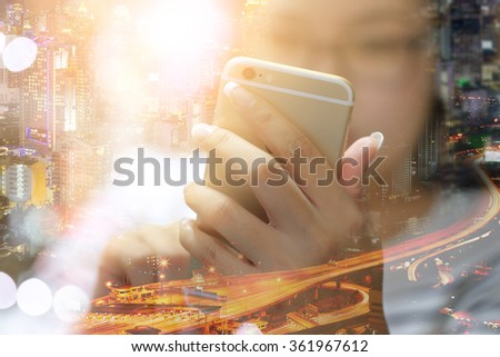 Double exposed of business woman using smartphone and city scape. selective focus at hand. - stock photo
