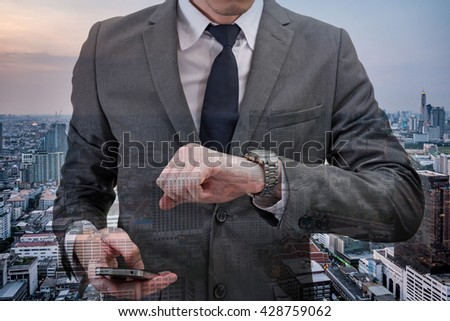 Double exposed of Businessman checking time on his wrist watch and holding mobile phone with cityscape. - stock photo