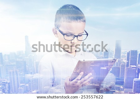 Double exposure boy and city. Young student using digital tablet with city skyline skyscraper view background. Modern new technology communication concept  - stock photo