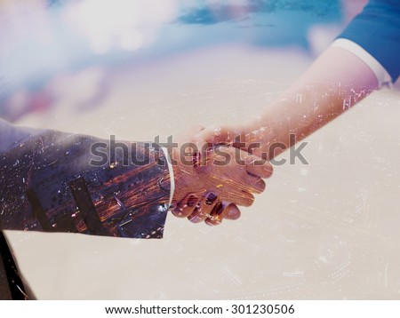 Double exposure design. Business partners concept with businessman and businesswoman handshake at modern office indoors - stock photo