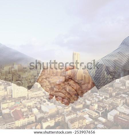Double exposure handshake - stock photo