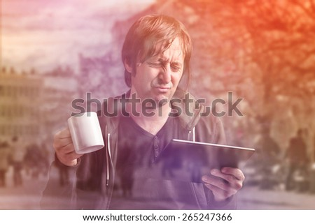 Double Exposure Image of Adult Caucasian Man Reading Bad News on Digital Tablet Computer Device and Drinking Coffee - stock photo