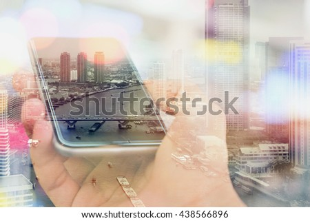 Double exposure image of businessman using smart phone with cityscape background, Business technology concept.