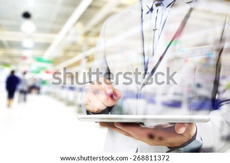Double exposure manipulation of Young handsome Business Man supervisor with tablet pc in the Shopping mall as Wireless Technology concept - stock photo