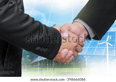Double Exposure of a businessman handshake on the background blurred. Concept of an agreement green energy. - stock photo