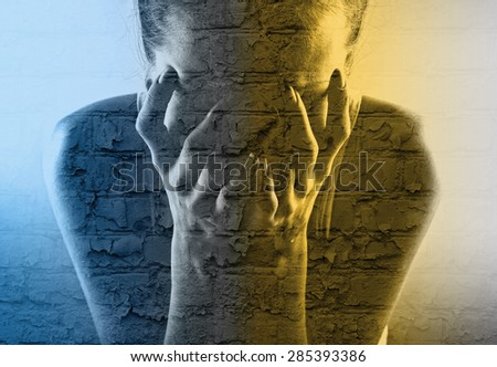 Double exposure of a crying young woman and an old brick wall - stock photo