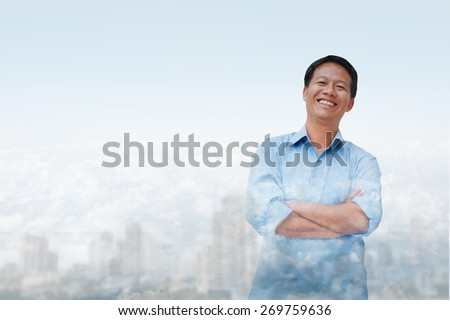 double exposure of asia business man 30 - 40 year old has city background .cross one's arm,Positive emotion - stock photo