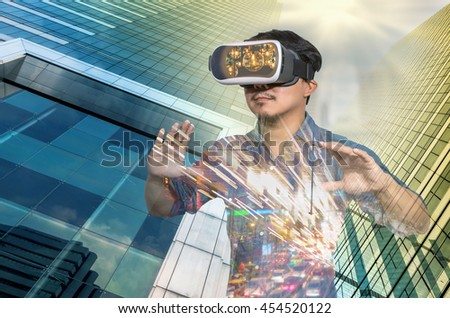 Double exposure of Asian man wearing virtual reality over the Modern business building glass of skyscrapers background, VR with business building concept - stock photo