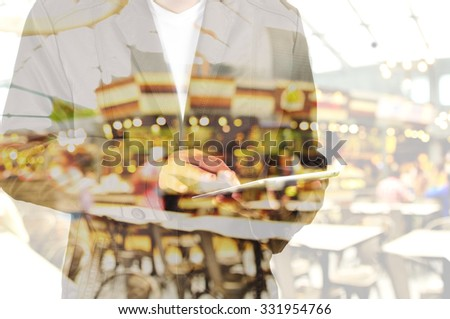 Double Exposure of Business Man using Mobile Tablet PC with Restaurant and Bokeh
