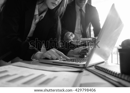 double exposure of business woman hand working on laptop computer and two colleagues discussing data on office desk with social media network diagram in morning light.black and white background  - stock photo