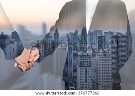 Double exposure of business women handshake and evening city as teamwork concept. - stock photo