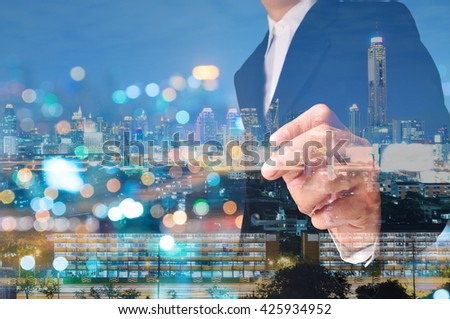 Double Exposure of Businessman draw Something with City Traffic Scene at Night and Building - stock photo