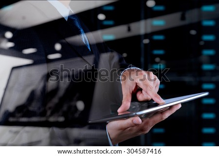 double exposure of businessman hand using tablet computer and server room background - stock photo