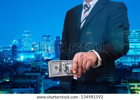 double exposure of businessman in black suite offering dollar money with night modern city building background