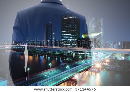 Double exposure of businessman in suit and cityscape at night. He's looking for his success in business and idea for life