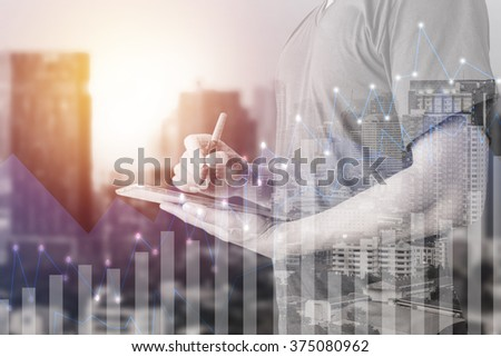 Double exposure of businessman using digital tablet with city landscape blurred background.Forex graph on the business city centre. A metaphor of international financial consulting.investment concept