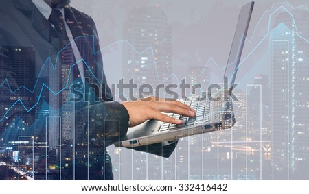 Double exposure of businessman using the laptop computer with cityscape and financial graph on blurred building background, Business Trading concept - stock photo