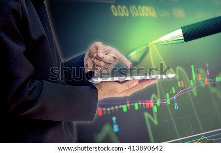 Double exposure of businessman using the tablet with financial graph on blurred pen and financial graph  background,  - stock photo