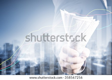 Double exposure of Businessman with money in hand and financial graph on cityscape blurred building background, investment, success and profitable business concepts,Business Trading concept - stock photo