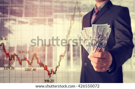 Double exposure of Businessman with money in hand with cityscape blurred building background, US dollar (USD) bills - investment, success and profitable business concepts,business background - stock photo