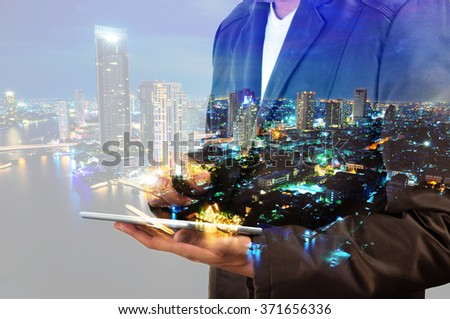Double exposure of city and businessman using digital tablet - stock photo