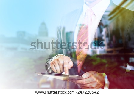 Double exposure of city and businessman using tablet.