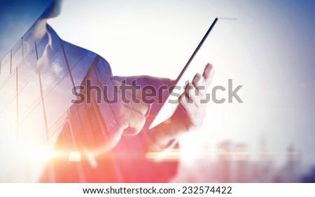 Double exposure of city and hands using digital tablet - stock photo