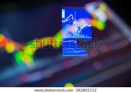 Double exposure of city businessman using a mobile device to check stock market data. on blurred stock market graph. background, Business Trading concept. - stock photo