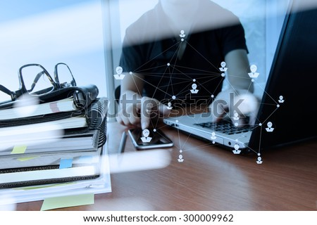 double exposure of designer hand working with digital tablet and laptop and notebook stack and eye glass with social network diagram on wooden desk in office - stock photo