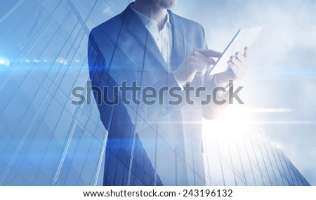 Double exposure of skyscraper and businessman with digital tablet - stock photo