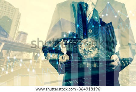 Double exposure of success businessman using digital tablet with graph on the business city centre. A metaphor of international financial consulting.(Elements of this image furnished by NASA) - stock photo