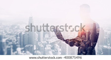 Double exposure photo bearded businessman wearing black shirt and glasses.Banker using contemporary notebook hands,work online banking.Panoramic view modern skyscraper city background.Soft light - stock photo
