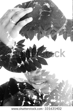 Double exposure portrait of a woman hiding her eyes with a hat combined with photograph of tree - stock photo