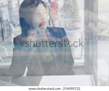 Double exposure portrait of an Asian working woman thinking of beach while she working in cafe. - stock photo