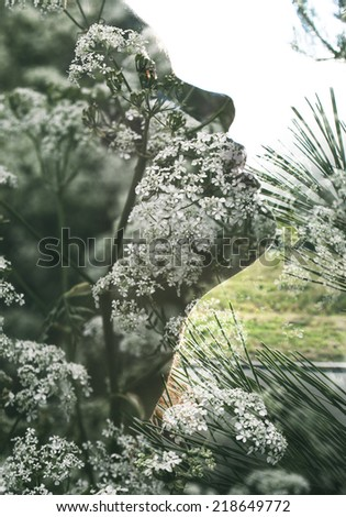 Double exposure portrait of attractive lady combined with photograph of flowers - stock photo