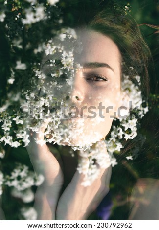 Double exposure portrait of elegant woman combined with photograph of white flowers - stock photo