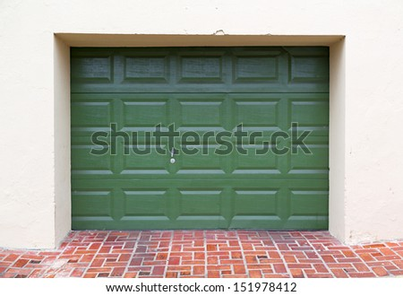 double green wooden garage door with paved driveway - stock photo