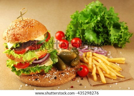 Double hamburger with fries on paper background - stock photo