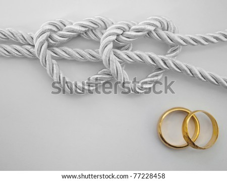 Double heart shaped silver rope tied and a double gold ring - stock photo