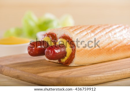 Double Hot Dog on a cutting board. Light roll.